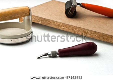 Cutter tool in front of block printing kit on white surface - stock photo