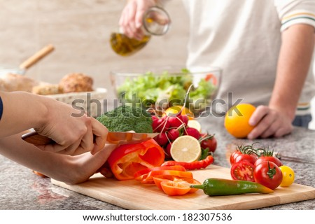 Cutting a vegetables for a salad with an olive oil - stock photo