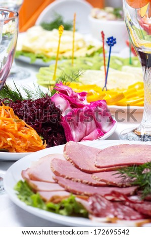 Cutting bacon, sausage and cured meat on a celebratory table - stock photo