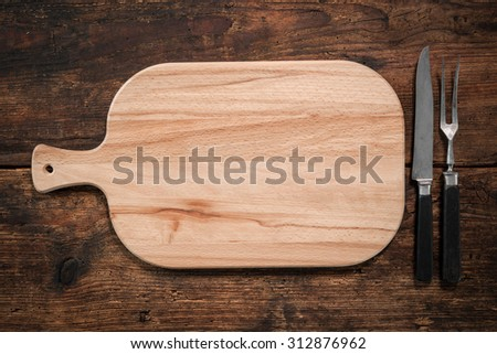 Cutting board, knife and fork on a rustic background. Lots of copy space - stock photo