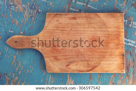 Cutting board on rustic wooden kitchen table as blank copy space for food, cooking and nutrition themes, vintage retro tone, top view - stock photo