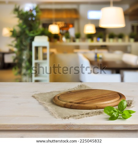 Cutting board on table over blurred restaurant interior background - stock photo