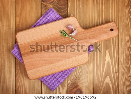 Cutting board over kitchen towel on wooden table background - stock photo