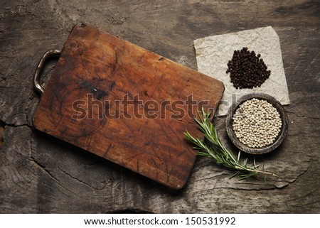 Cutting Board, rosemary and spices on a old wooden table - stock photo