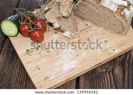 Cutting Board with Bread and vegetables - stock photo