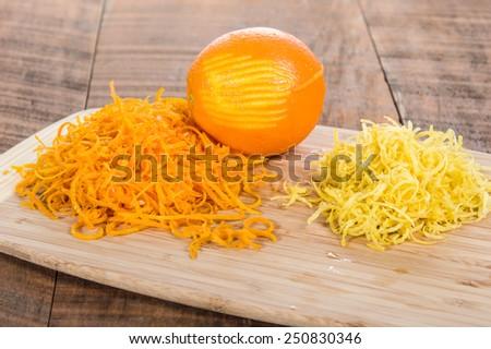 Cutting board with orange and lemon zest - stock photo