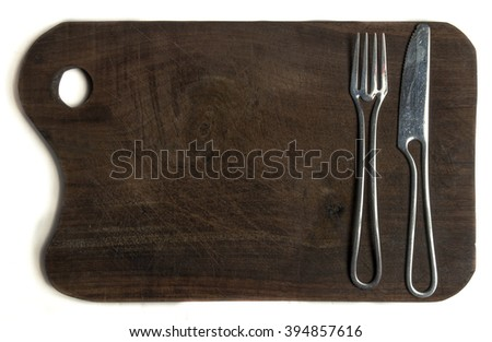 cutting board with silver knife and fork, ideal to place text in the middle - stock photo