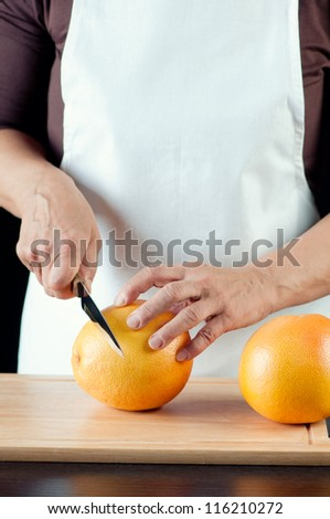 Cutting grapefruits, vertical shot - stock photo
