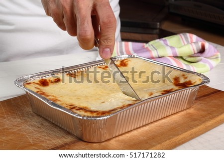 Cutting Lasagne Bolognese in Disposable Foil Dish