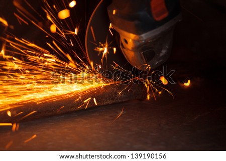Cutting metal with many sharp sparks - stock photo