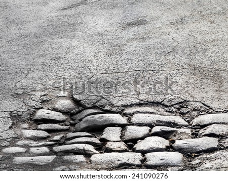 Cutting of an old road with cracked asphalt and a gully in the center of cobblestones  - stock photo