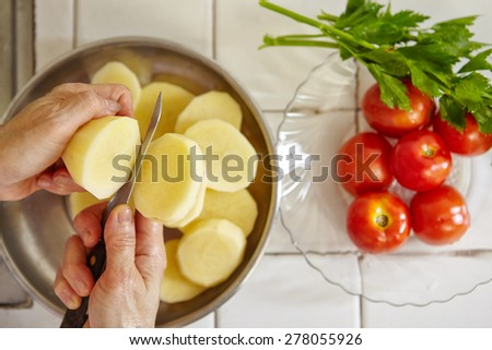 Cutting potato in big slice. Tomato and parsley on background - stock photo