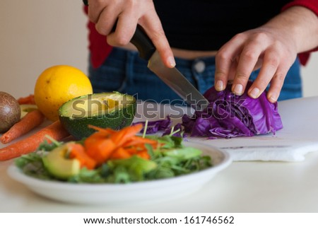 cutting red cabbage for a green salad