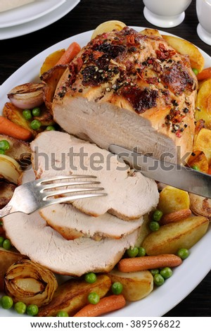 cutting roasted turkey breast slices with vegetables - stock photo