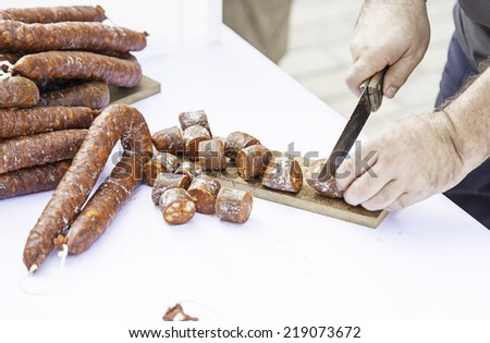 Cutting sausage with a knife, detail of a chef cutting food - stock photo