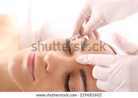 Cutting scars woman during treatment with dermatologist.Caucasian woman during surgery using a scalpel - stock photo