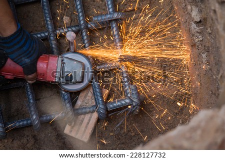 Cutting steel with a small grinder - stock photo