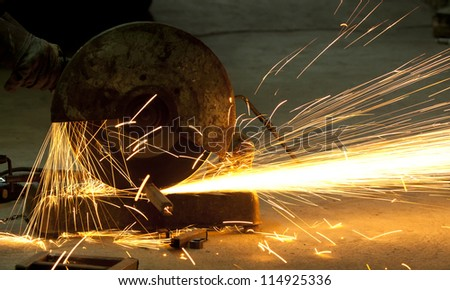 cutting steel with machine for cutting steel by worker - stock photo