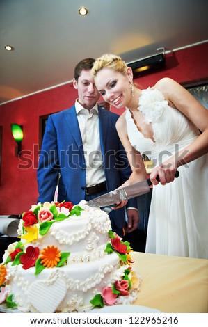 Cutting the cake newlyweds on wedding day - stock photo