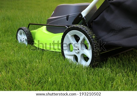 cutting the grass with lawn mower - stock photo