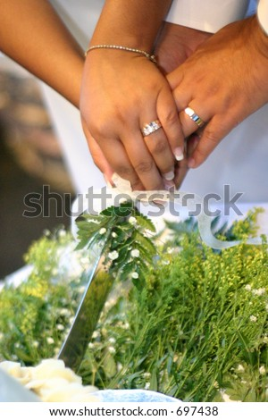 cutting the wedding cake with hands overlapping - stock photo