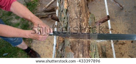 cutting trees for firewood, hand saw cutting
