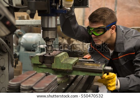 Cutting work pieces. Portrait of a young metalworker wearing uniform and protection glasses operating high precision milling machine at the production plant looking closely at the drill
