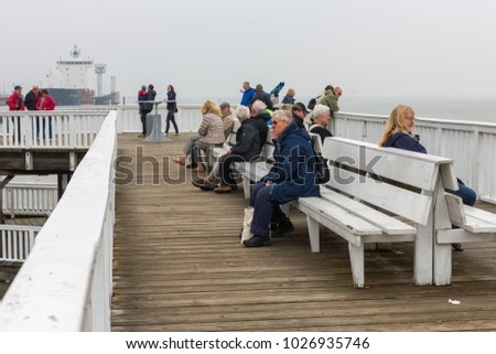 CUXHAVEN, GERMANY - MAY 19, 2017: People at wooden pier of Cuxhaven waiting for ferry to German island Helgoland. The weather is hazy.