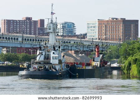 Cuyahoga River Tug    A tug boat slowly maneuvers a barge filled with rock and sand around one of the many bends in the Cuyahoga River in Cleveland, Ohio - stock photo