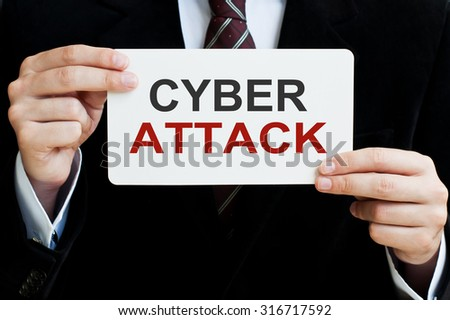 Cyber Attack. Man holding a card with a message text written on it - stock photo