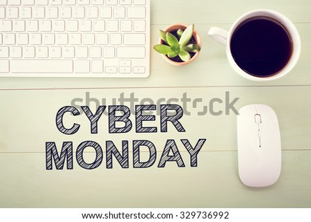 Cyber Monday message with workstation on a light green wooden desk - stock photo