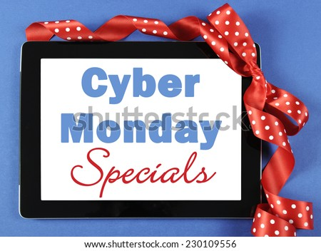 Cyber Monday Specials sale shopping sign on black computer tablet device on blue background with red polka dot ribbon. - stock photo