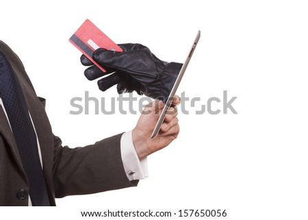 Cyber theft being committed through a tablet computer. A man wearing a suit is holding a tablet computer while a hand is reaching through screen to steal credit card. white background.  - stock photo