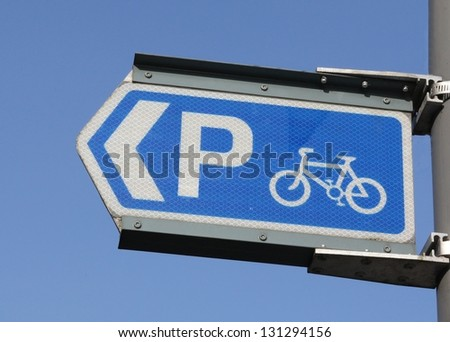 Cycle directional parking sign against a blue sky. - stock photo