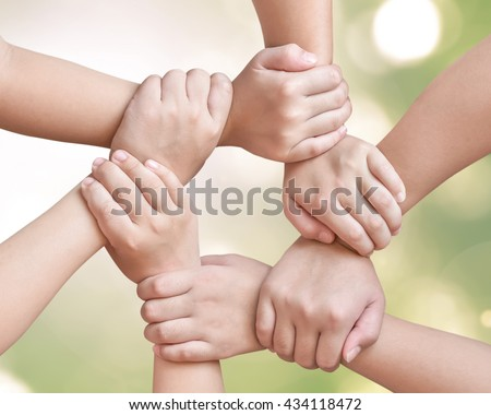 Cycle of children young generation's hands holding together isolated on blur green environment background: Circle ring of people friendship connectivity togetherness unity: Global linkage CSR concept - stock photo