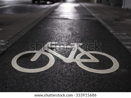 Cycle path lane sign in a wet urban street. - stock photo