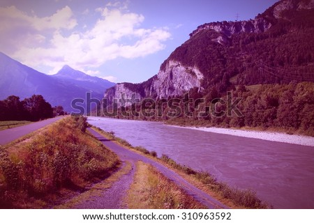 Cycle track along Rhine river in Switzerland. Mountain landscape. Retro filtered color style. - stock photo