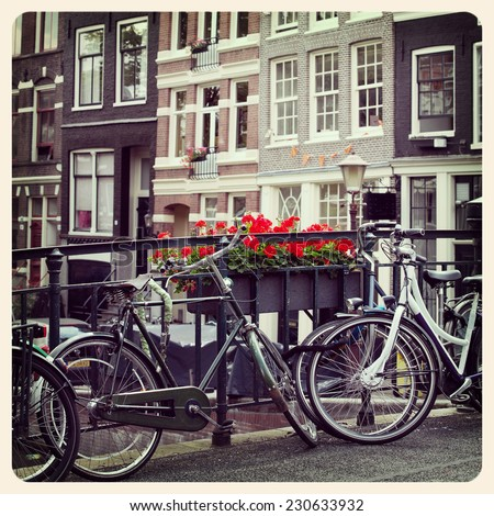 Cycles on a canal bridge with the historic houses of Amsterdam in the background. Processed to look like an aged, instant photo.  - stock photo