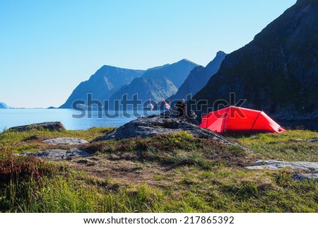 Cycling and camping at Lofoten Island. Lonely red tent pitched up by cyclist. - stock photo