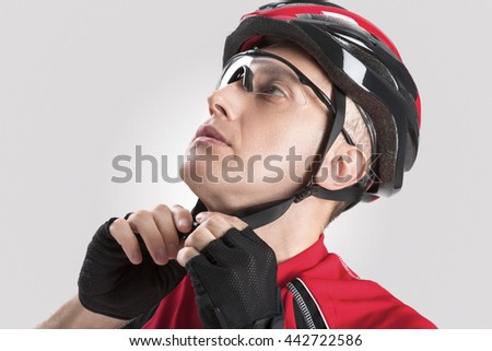 Cycling Safety Concept and Ideas. Portrait of Male Caucasian Cyclist Putting On Helmet. Against White Background. Horizontal Image - stock photo