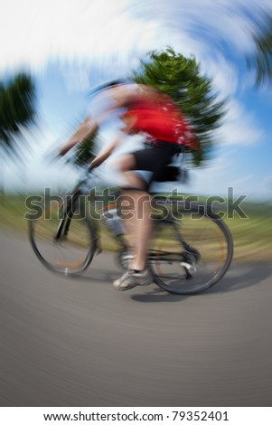 Cycling series: biker cycling outdoors (fisheye lens distortion and motion blur are used to convey dynamic movement) - stock photo