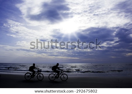 Cycling silhouette children.Sea background - stock photo