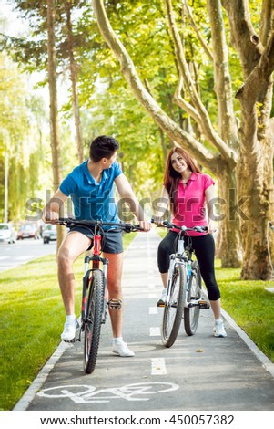 Cycling young couple. In the park. Beautiful bicycle lane