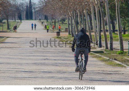 Cyclist. A biker man cycling with his bicycle in a park