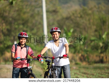 cyclist couple smiling at camera on mountain trail on a sunny day - stock photo