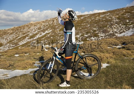 Cyclist drinking water. - stock photo