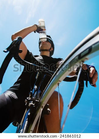 Cyclist drinking water over blue sky - stock photo