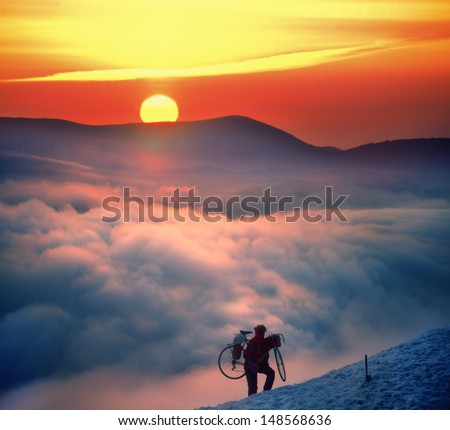 Cyclist extreme, during a beautiful sunrise raises road bike to the top of the mountain where there is snow - stock photo