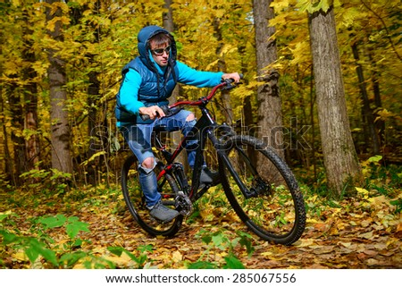 Cyclist extreme riding mountain bike through impassable dried bushes in wild autumn colorful forest  - stock photo