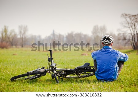 Cyclist have a rest with bike on spring day  - stock photo
